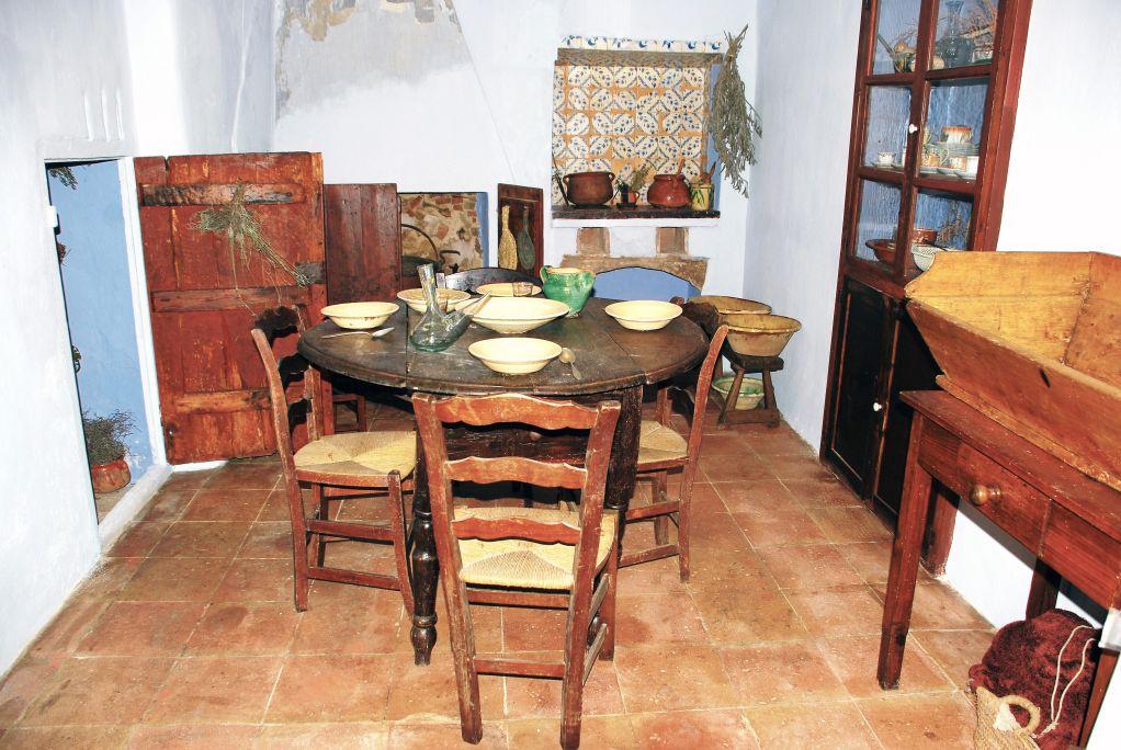 Cocina antigua de Can Cinto Xuà, con la mesa puesta, la chimenea, los fogones de carbón y la despensa