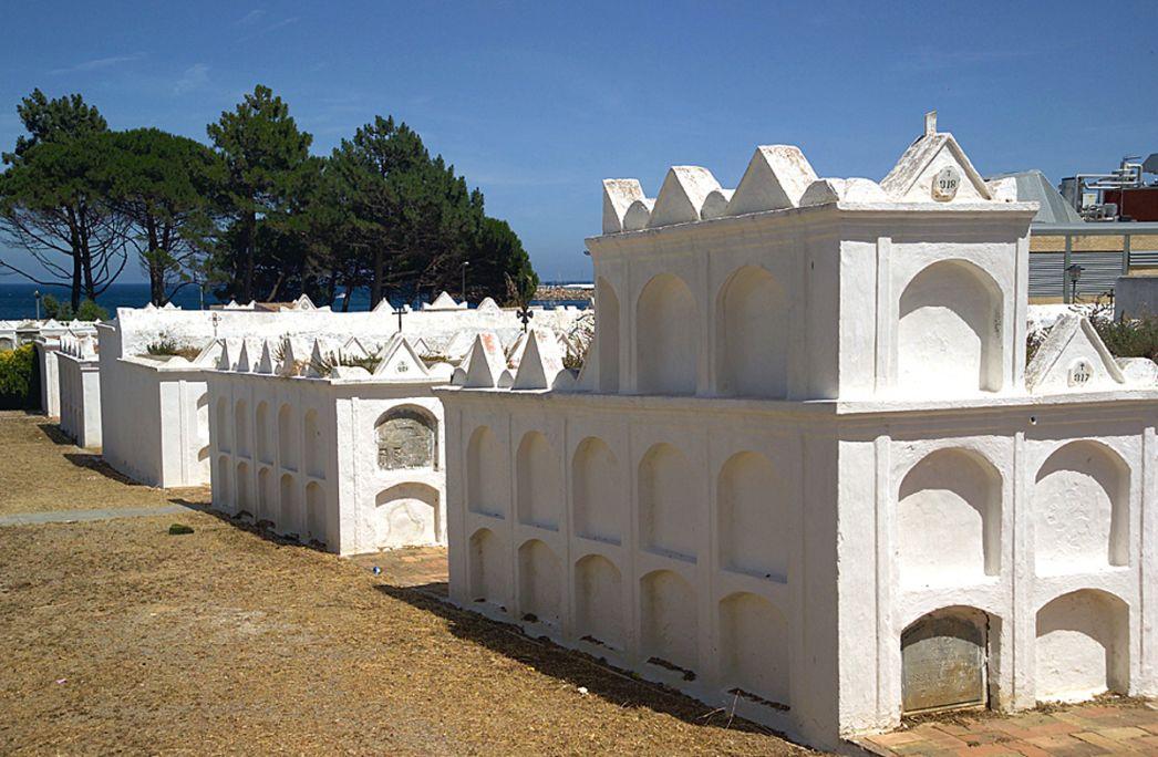Vista de los nichos rematados con tímpanos triangulares, todo pintado de blanco y con el mar de fondo.