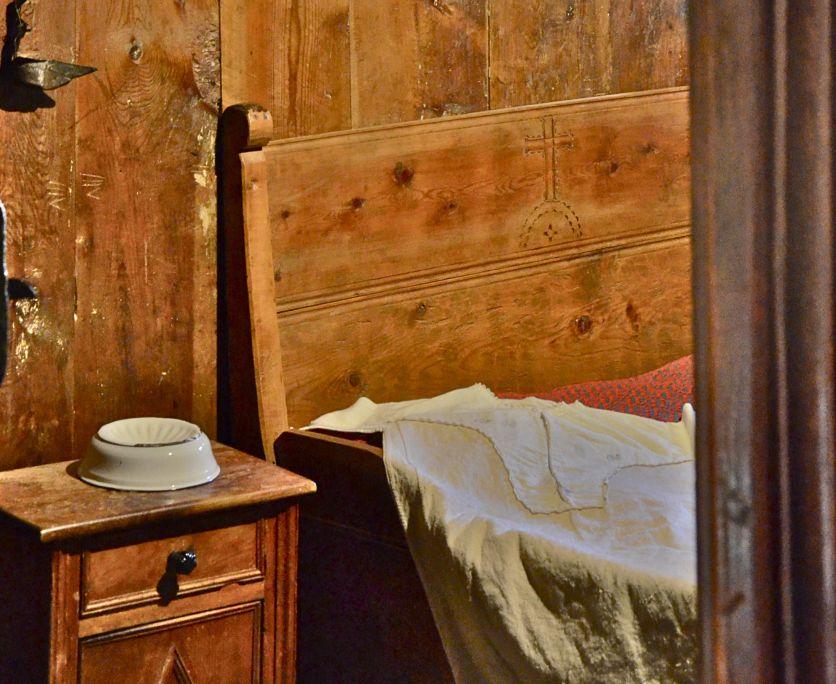 El llit, com altres peces del mobiliari, incorpora elements de caire religiós i de protecció.