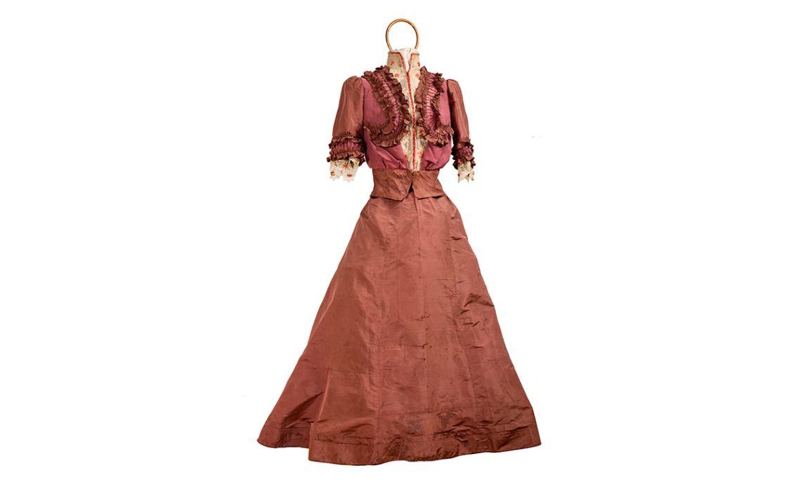 Vestit llarg de cotó del segle XIX, guarnit amb delicat vellut verd