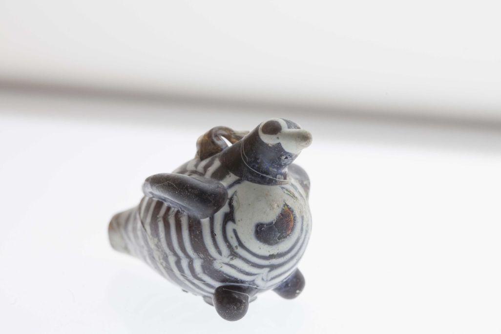 Petit contenidor de vidre bufat en forma d'ocellet amb un orifici en la cua. Origen desconegut. Segle IV dC