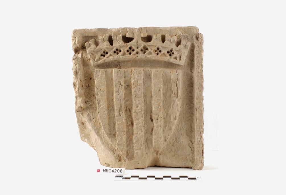 Placa amb escut reial, segona meitat del segle XIV, pedra calcària, procedent del Reial Monestir de Santa Maria de Santes Creus, Aiguamúrcia. © de la fotografia: Museu d'Història de Catalunya