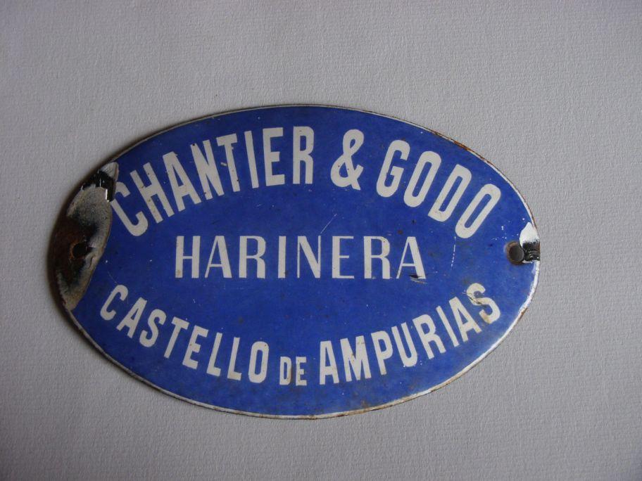 Placa metàl·lica amb la inscripció Chantier and Godó, els arrendataris de la fàbrica de farines de Castelló d'Empúries al 1920.