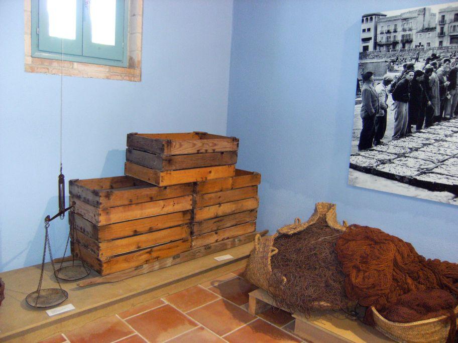 Caixes de fusta esperant ser omplertes de peix per a la subhasta, situades sobre un baiard per ser transportades.