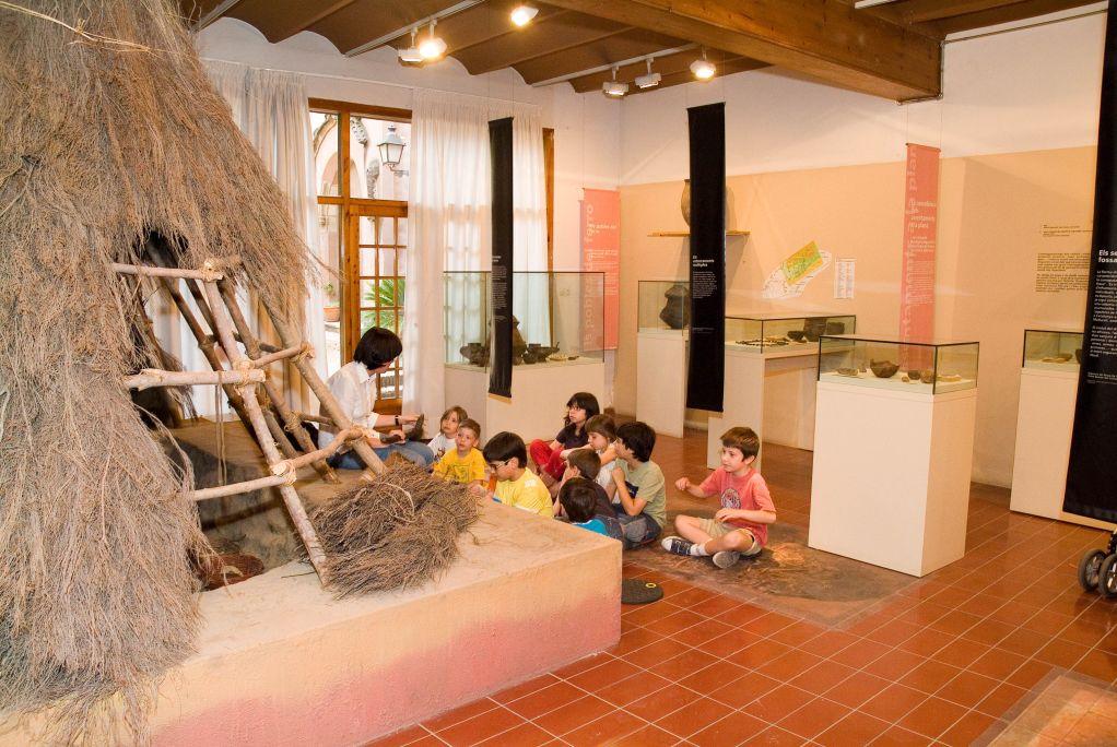 Vista de la sala «Els primers assentaments pagesos i l'expansió pel territori» i, en un primer pla, la rèplica d'una cabana prehistòrica
