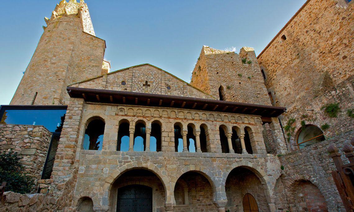 Porta Ferrada i façana de l'església romànica, flanquejada per les torres del Fum i del Corn