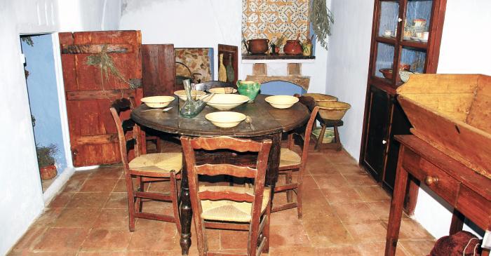 <p>Cocina antigua de Can Cinto Xu&agrave;, con la mesa puesta, la chimenea, los fogones de carb&oacute;n y la despensa</p>