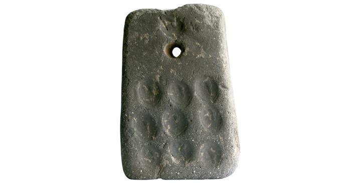<p><em>En algunos de estos pondus podemos observar diferentes marcas como incisiones geom&eacute;tricas y marcas de una piedra de anillo. </em></p>