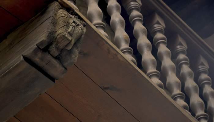 <p>Detall de la balconada, que combina decoraci&oacute; tornejada i una cara humana al suport inferior.</p>