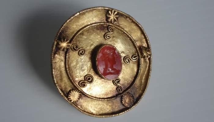<p>Reproducci&oacute;n de un disco de oro con la aplicaci&oacute;n de un camafeo oval.</p>